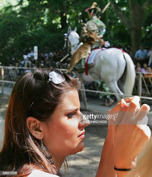 Miss France Cynthia Tevere takes a picture of a rider during an annual shito festival 'Yabusame' Japanese traditional archery on horseback at the...