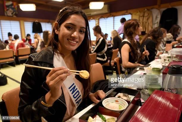 Miss India Ankita Kumari eats 'Tempura' with other Miss International Beauty Pageant contestants at the SushiZanmai restaurant near the Tsukiji fish...
