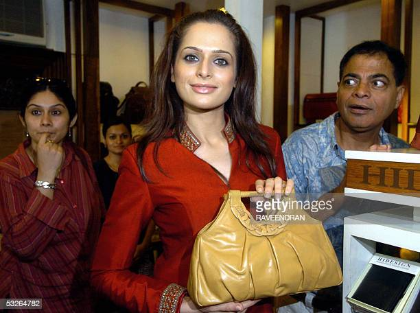 Miss IndiaUniverse 2005 Amrita Thapar is surrounded by inquisitive bystanders as she poses with a bag from the new 'Riviera' collection from...