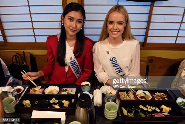 Miss Indonesia Kevin Lilliana and Miss South Africa Tayla Skye Robinson pose at the SushiZanmai restaurant near the Tsukiji fish market in Tokyo on...
