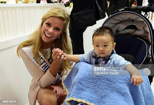 Miss International contestant, Miss Netherlands Rache van der Meulen smiles with a baby boy as she shops at Tokyo's Isetan department store on...