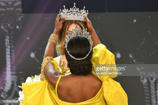 Miss International Queen 2020 winner Mexico's Valentina Fluchaire is presented her crown by 2019 winner Jazelle Barbie Royale of the US during the...