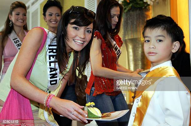 Miss Ireland Mary Gormley smiles while taking a fruit sample from a Thai boy at a Thai fruit introduction event in a hotel in Bangkok 12 May 2005...
