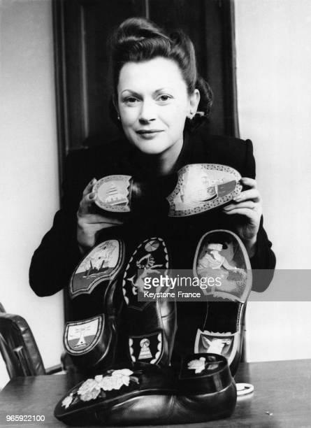 Miss Joan Verney observe plusieurs exemplaires de chaussures en cuir décorées dans le cadre d'un concours le 31 janvier 1949 à Londres RoyaumeUni