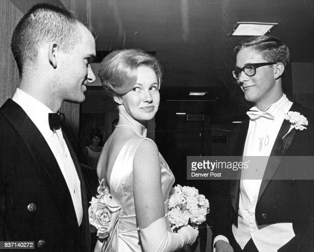Miss Kimbrough Street whirls around to display her gown to ball escorts Cadet Charles David Jones left and John Walter Hyer III Miss Street attends...