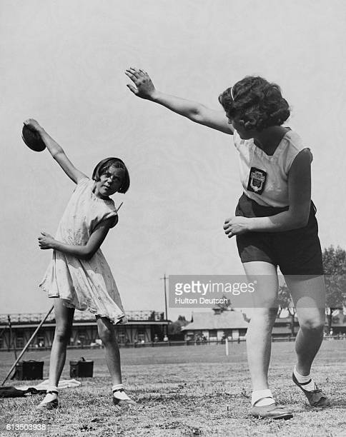 Miss L Fawcett the British javelin and discus thrower coaches her elevenyearold niece Doreen Imisson at Paddington Recreation Ground while in...