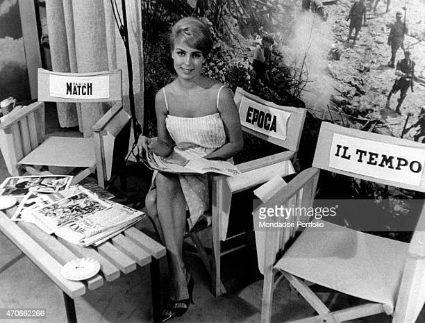 Miss Laura Rosci smiles at the camera while leafing through the pages of a magazine sitting on a sponsorized chair in the press office of Dino de...