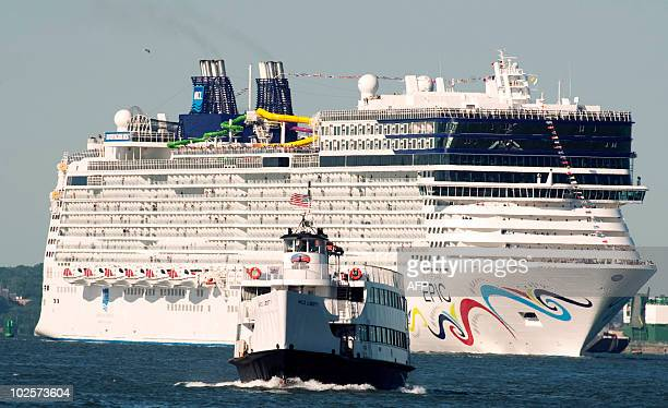 Miss Liberty is dwarfed by the cruise ship Norwegian Epic as she sails through New York Harbor July 1 2010 in New York The Norwegian Cruise Line ship...