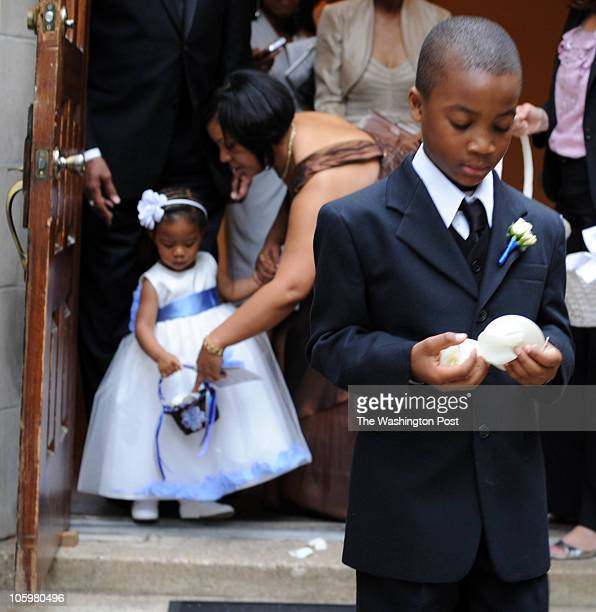 Miss MacKenzie Allen holds flower petals that will be tossed as the bride and groom exit the church on April 24 2010 Master Marcus Delle is also...