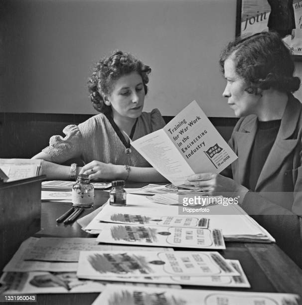 Miss Maude Filkins is assisted by Miss Gregory, the interviewing officer at Kings Cross Employment Exchange, as she registers for war work at the...