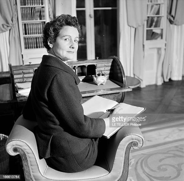 Miss Nancy Mitford. La célébre romancière anglaise Nancy MITFORD, assise dans un fauteuil, écrivant sur un cahier.