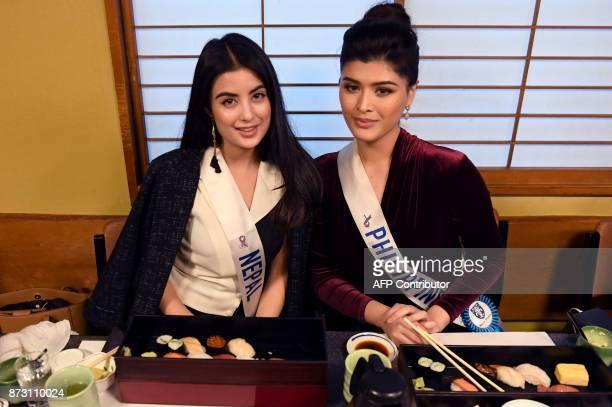 Miss Nepal Niti Shah and Miss Philippines Maria Angelica De Leon pose at the SushiZanmai restaurant near the Tsukiji fish market in Tokyo on November...