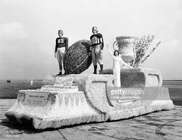Miss New Orleans waves with two uniformed football players aboard her Sugar Bowl float as it will appear in the Miss America parade on the Boardwalk...