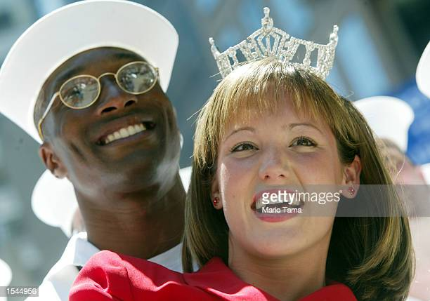 Miss New York Andrea Plummer poses for photographs with US Navy E6 Jeff Joseph from Adelphi Maryland in Times Square May 23 2002 in New York City The...