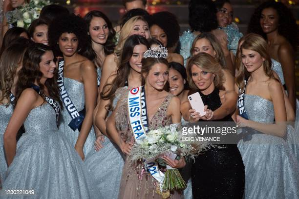 Miss Normandie Amandine Petit poses for a selfie with Miss France Organisation general director Sylvie Tellier and contestants the end of the Miss...
