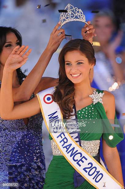 Miss Normandie Malika Menard receives the crown from 2009 Miss France Chloe Mortaud during the 2010 Miss France Beauty pageant at Palais Nikaia on...