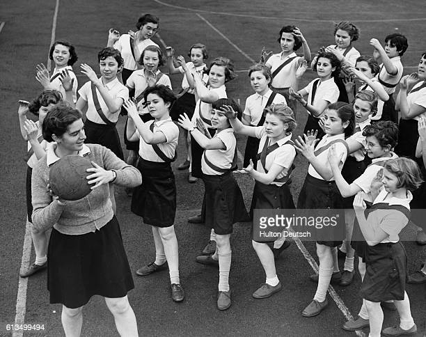 Miss P J Edgeley takes a class of girls from Stepney's Central Foundation School through warmup exercises before a netball game at the Coram Fields...