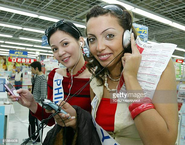 Miss Philippines Margaret Ann Bayot and Miss Turkey Gulsah Sahin try iPod players as they visit a discount shop in Tokyo 03 October 2004 61...