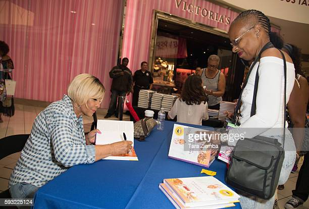 Miss Robbie signs her book Sweetie Pie's Cookbook Soul Southern Recipes From My Family To Yours for a fan at the Leimert Park Village Book Fair at...