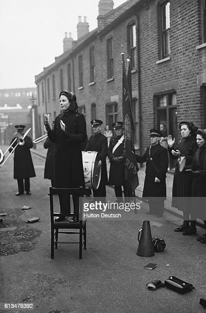 Miss Ross a Salvation Army worker plays her tambourine accompanied by other members of the band at an open air meeting