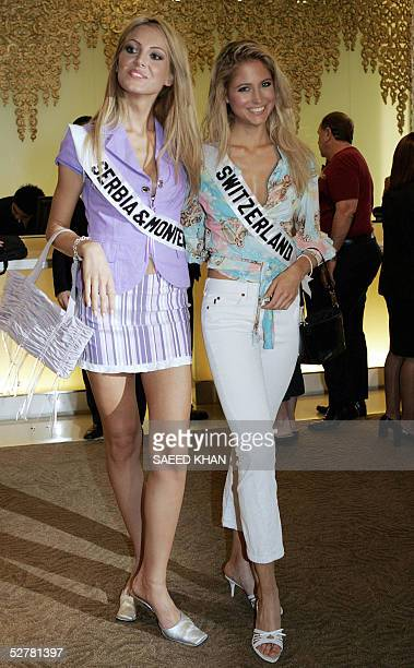 Miss SerbiaMontenegro Jelena Mandic smile along with Miss Switzerland Fiona Hefti as they walk in a hotel lobby in Bangkok 10 May 2005 Mendic and...