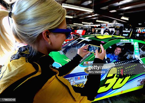 Miss Sprint Cup Brooke Werner takes a picture of David Stremme driver of the Lean1 Toyota sitting in his car in the garage during practice for the...