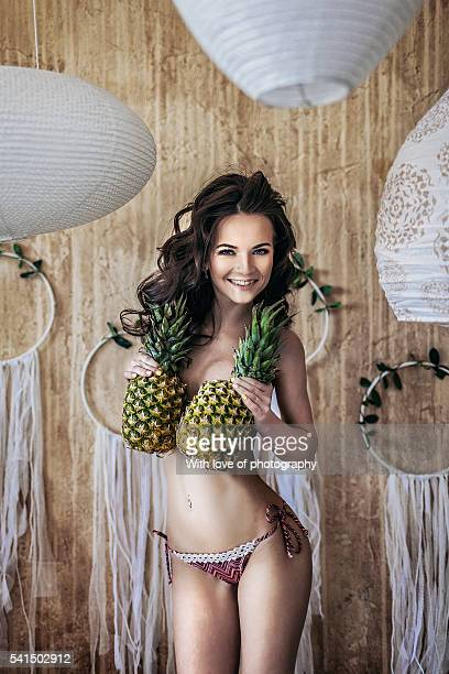 Miss summertime, attractive caucasian girl in bikini with pineapples in tropic style