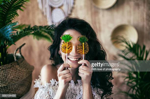 Miss summertime, cheerful smiling attractive caucasian girl in bikini with pineapples lollipops in tropic style