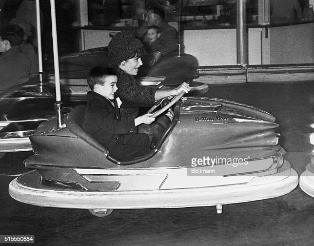 2/11/1961 Miss Taylor and her son Michael both grit their teeth in mock anger as they wheel around in an electric bumpercar in the circus rides area