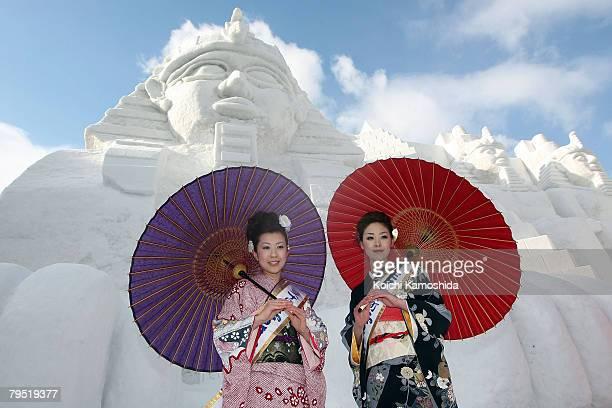 Miss Tokamachi Akiko Suga and Mayumi Ota pose in front of the snow sculptures Relics of Egypt prepared for Sapporo Snow Festival 2008 at Odori Park...