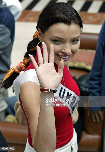 Miss Ukraine Oleksandra Nikolayenko waves at photographers as she walks across the hotel hall 30 May 2004 in Quito Ecuador where the Miss Universe...