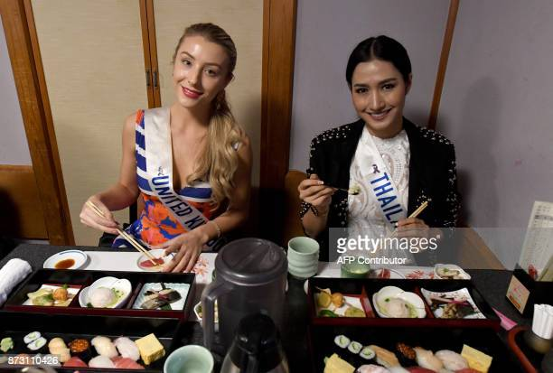 Miss United Kingdom Ashley Powell and Miss Thailand Ratiyaporn Chookaew pose at the SushiZanmai restaurant near the Tsukiji fish market in Tokyo on...