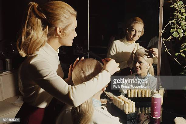Miss United Kingdom Yvonne Anne Ormes combs the hair of of Miss Ireland Mary Elizabeth McKinley prior to competition in the Miss World 1970 beauty...