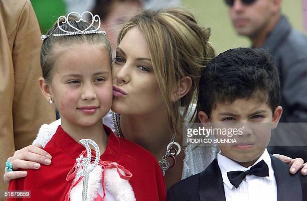 Miss Universe 2004 Australian Jennifer Hawkings kisses Dayana Echeveria Queen of the Carcelen school next to schoolmate Carlos Peralta in Quito...