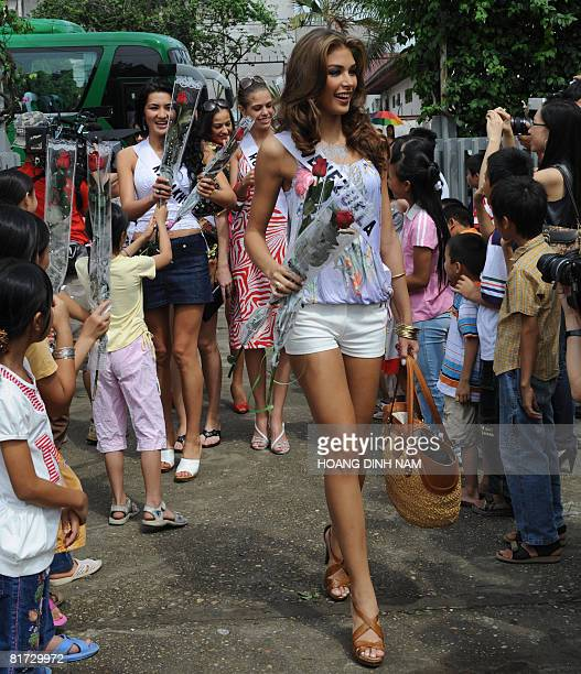 Miss Universe 2008 contestant Dayana Mendoza Miss Venezuela and other contestants are greeted by children as they arrive at Hanoi's SOS village on...