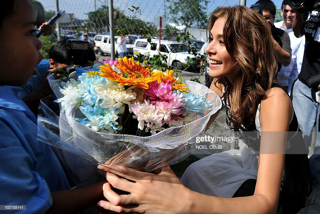 Miss Universe 2008 Dayana Mendoza (R) receives flowers from an elementary student from Tondo, a slum area in Manila on June 16, 2010. The Venezuelan beauty was named Smartmatic's 'Ambassador of Transparency' and flew to Manila for a three day tour to join the celebrations over the success of the automated elections.