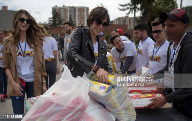 Miss Universe 2008 Venezuelan Dayana Mendoza and Miss Universe 2009 Venezuelan Stefania Fernandez help to sort donations during the Healing event to...
