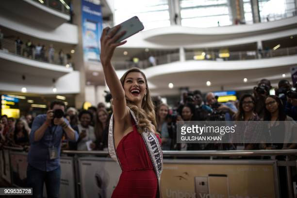 TOPSHOT Miss Universe 2017 DemiLeigh NelPeters takes a 'selfie' as she arrives home to South Africa for the first time after being crowned at OR...
