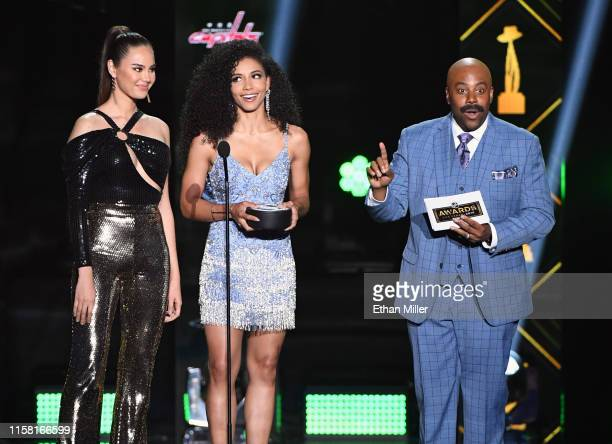 Miss Universe 2018 Catriona Gray and Miss USA 2019 Cheslie Kryst present the James Norris Memorial Trophy as host Kenan Thompson as his character...