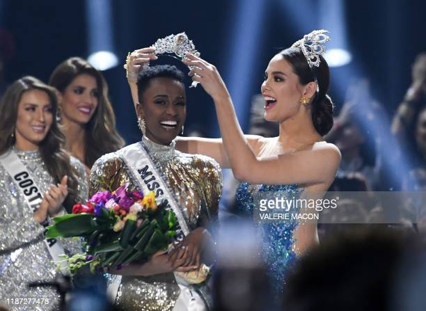 Miss Universe 2018 Philippines' Catriona Gray puts the crowns on the head of the new Miss Universe 2019 South Africa's Zozibini Tunzi on stage during...