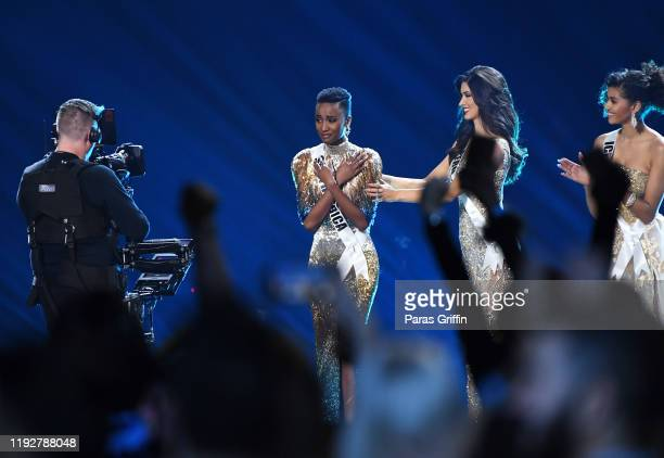 Miss Universe 2019 Zozibini Tunzi of South Africa appears onstage with Miss Iceland Birta Abiba and Miss Peru Kelin Rivera at the 2019 Miss Universe...