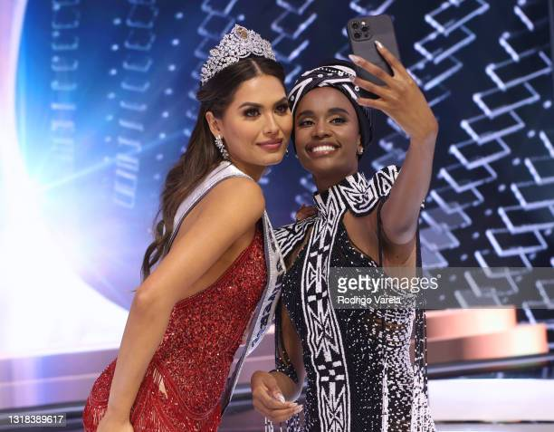Miss Universe 2020 Andrea Meza and Miss Universe 2019 Zozibini Tunzi take a selfie onstage at the 69th Miss Universe competition at Seminole Hard...