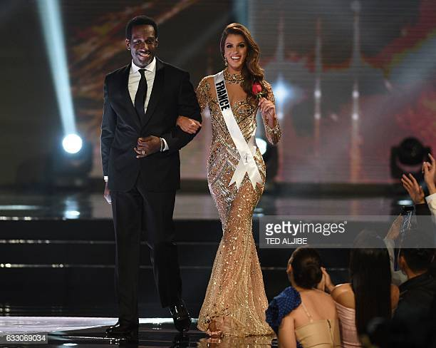 Miss Universe candidate Iris Mittenaere of France walks with a member of US artist Boyz II Men on stage during the finals of the Miss Universe...