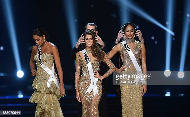 Miss Universe candidates Iris Mittenaere and Raquel Pellisier of Haiti is placed with headphones as Andrea Tovar of Colombia prepares to take a...