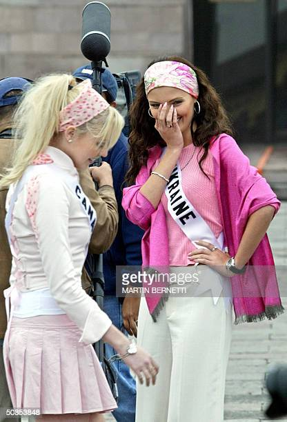 Miss Universe candidates Venessa Fisher of Canada and Oleksandra Nikolayenko of Ukraine pose for TV cameramen in front of the Middle of the World...