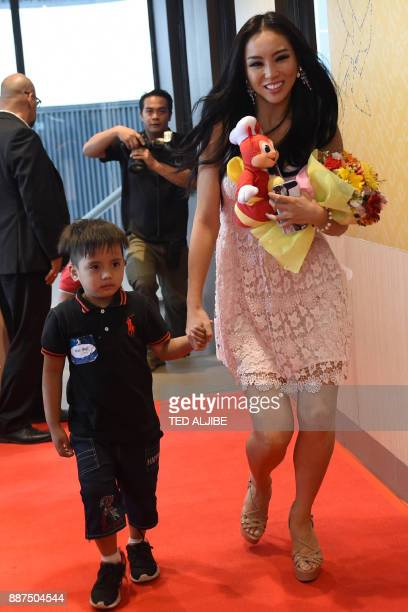Miss Universe contestant Cho Se Whee Of South Korea walks with a child from an orphanage during a visit to a popular fast food restaurant in Manila...