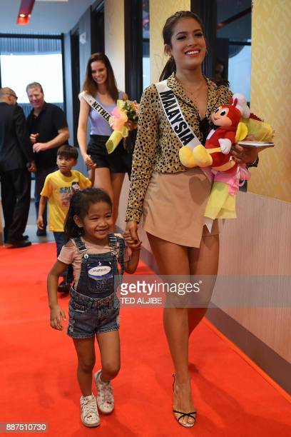 Miss Universe contestant Samantha James of Malaysia walks with a child from an orphanage during a visit to a popular fast food restaurant in Manila...
