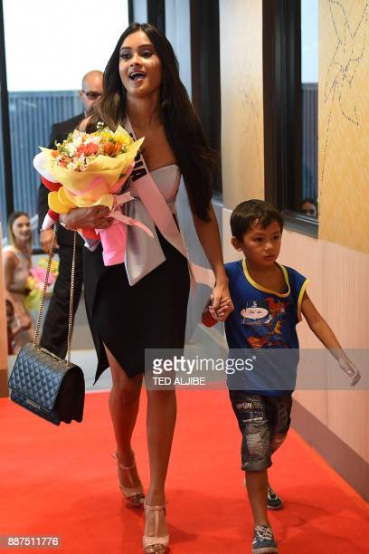 Miss Universe contestant Shraddha Shashidhar of India walks with a child from an orphanage during a visit to a popular fast food restaurant in Manila...