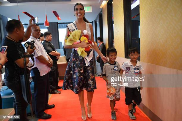 Miss Universe contestant Sofia del Prado of Spain walks with children from an orphanage during a visit to a popular fast food restaurant in Manila on...