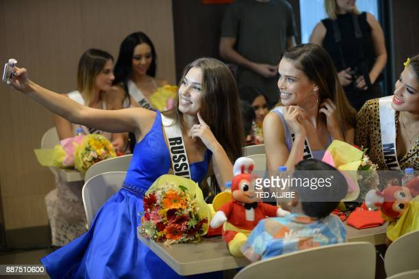 Miss Universe contestants Kseniya Alexandrova of Russia Nicky Opheij of the Netherlands and Samantha James of Malaysia take a selfie with children...